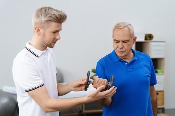 trainer unterstützt einen senior beim training mit hanteln