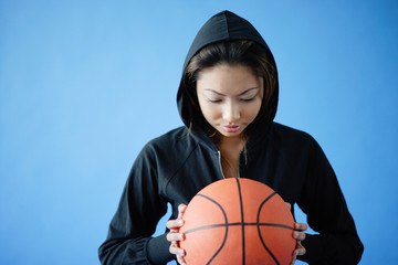 Woman wearing hooded shirt, holding basketball