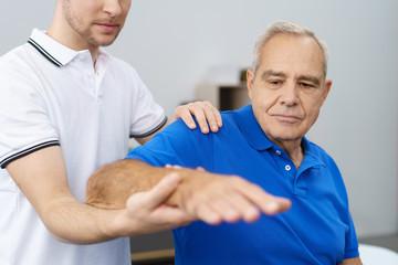 orthopäde untersucht die schulter eines älteren patienten