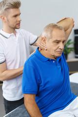 physiotherapeut untersucht die schulter eines älteren mannes in der praxis