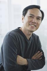 Man smiling at camera, arms crossed