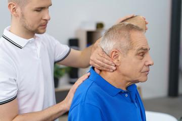 therapeut untersucht einen älteren mann am oberen rücken