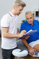 therapeut bespricht etwas mit dem patieten und zeigt auf clipboard