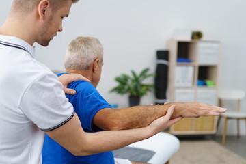 therapeut behandelt einen älteren mann an der schulter