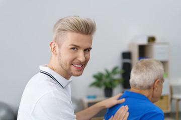 physiotherapeut in seiner praxis mit einem älteren patienten