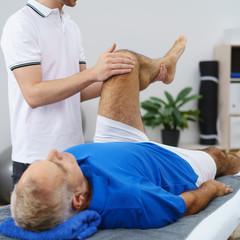 therapeut untersucht das knie eines älteren mannes