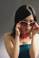 Woman adjusting large sunglasses, looking at camera