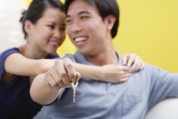 Woman embracing man from behind, man holding keys