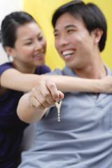 Couple embracing, man holding keys,