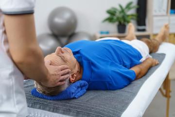 therapeut massiert einen älteren mann an der stirn