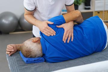 therapeut untersucht die schulter eines älteren mannes