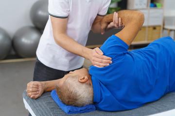 physiotherapeut behandelt einen mann an der schulter