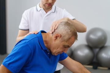 therpeut untersucht einen älteren patienten in der praxis