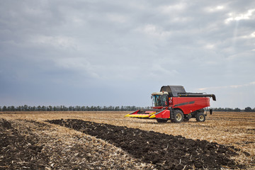 Fototapete - Red harvester working in a field
