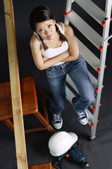 Young woman sitting on ladder, arms crossed, looking at camera