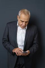 älterer mann tippt auf seinem mobiltelefon