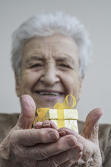 Happy senior woman holding gift on her hands