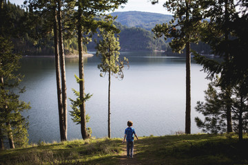 Boy walking towards lake