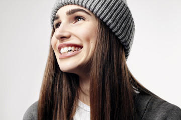 Young pretty beautiful woman in a grey outfit. Closeup portrait of smiling face. Winter clothes.
