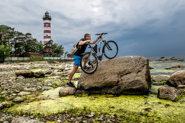 A cyclist pushes his bike on a huge rock in the background Shepe