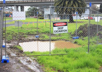 Deep excavation with chain link fence and warning sign in urban setting