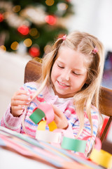 Christmas: Girl Working On Her Paper Chain Garland For Christmas