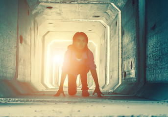 Backlight of a teenager depressed sitting inside a dirty tunnel