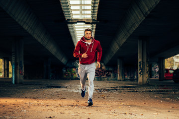 Man in red hoodie running under overpass