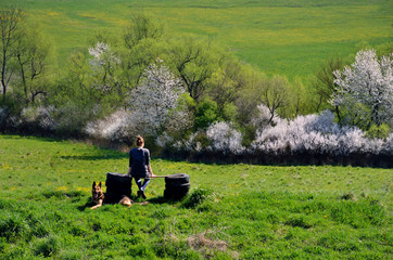 Friendship between young girl and her dog on beautiful spring meadow, where girl sitting in calm atmosphere