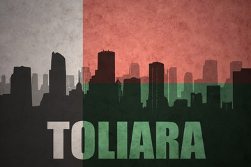 abstract silhouette of the city with text Toliara at the vintage madagascar flag