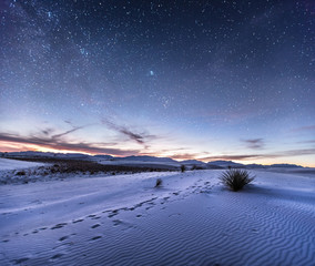 Sand dunes with footprints in the desert under night sky, New Mexico