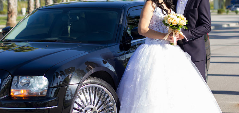 Bride and groom standing in front of wedding car