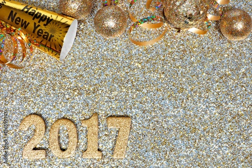 new years eve top border of streamers and decor with 2017 numbers over a golden background