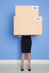 Businesswoman holding heavy boxes on blue wall background