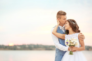Portrait of beautiful wedding couple near river, close up view