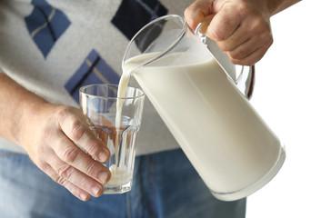 Senior man pouring milk into glass