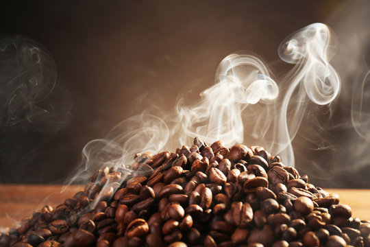 Coffee beans with smoke on dark background