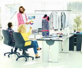 modern designer and his team choose the fabric for clothes