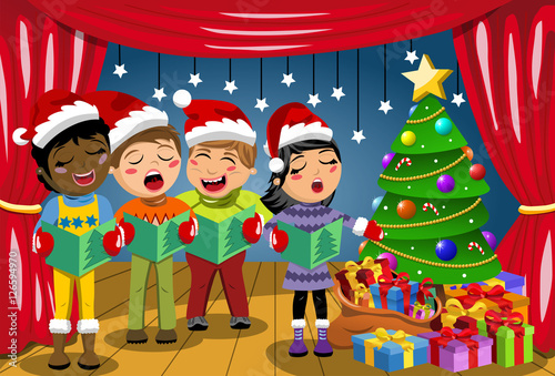 19cf99fa85aaa Multicultural kids wearing xmas hat singing Christmas carol nativity play  stage
