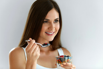 Portrait Of Smiling Woman Eating Yoghurt With Oats And Berries