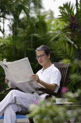 Mature man sitting in garden, reading newspaper