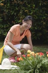 Woman tending to flower bed in garden