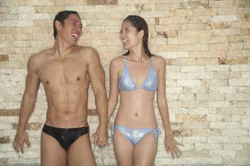 Couple in swimwear, holding hands, standing under running water