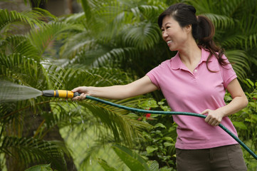 Woman holding garden hose, watering plants