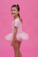 Young girl in ballet outfit, turning to smile at camera