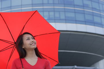 Woman with red umbrella, looking up