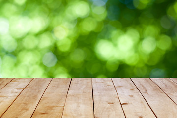 Wood table top on green bokeh background.