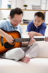 Father playing the guitar, son watching him