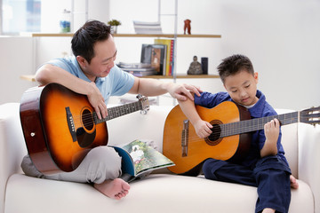Father teaching son to play the guitar