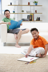 Father sitting on sofa, son on floor with drawing pad